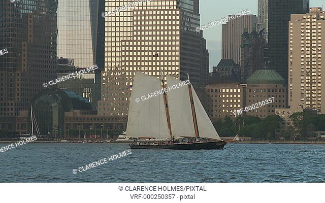 A two-masted schooner sails south on the Hudson River past Battery Park City and the North Cove Marina in New York City