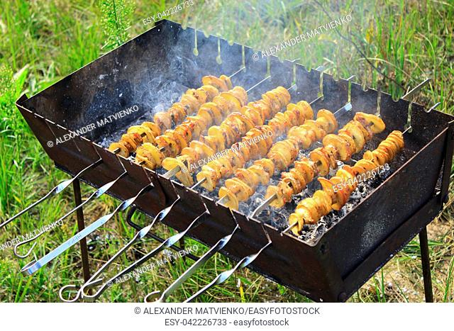 Shashliks from pieces of potatoes and bacon. Cooking of potatoes and bacon on fire. Picnic at nature. Barbecue lunch. Marinated shashlik from potatoes and bacon...