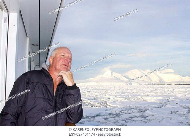 Man standing on cruise ship balcony admiring ice field at entrace to Lemaire Channel, Antarctica