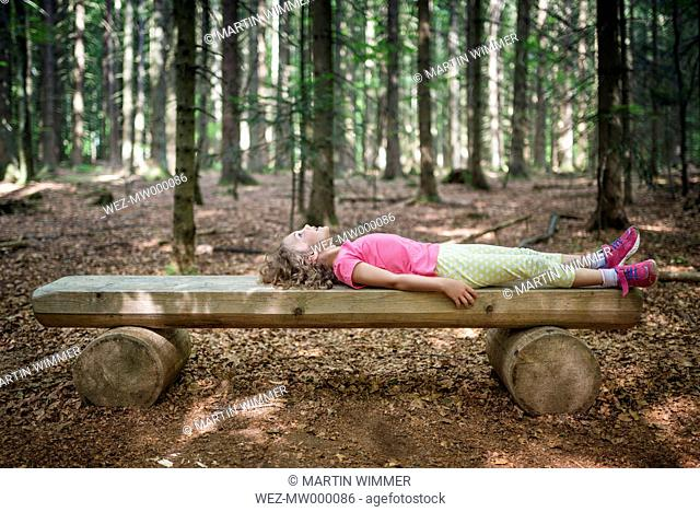 Girl lying on wooden bench in forest looking up