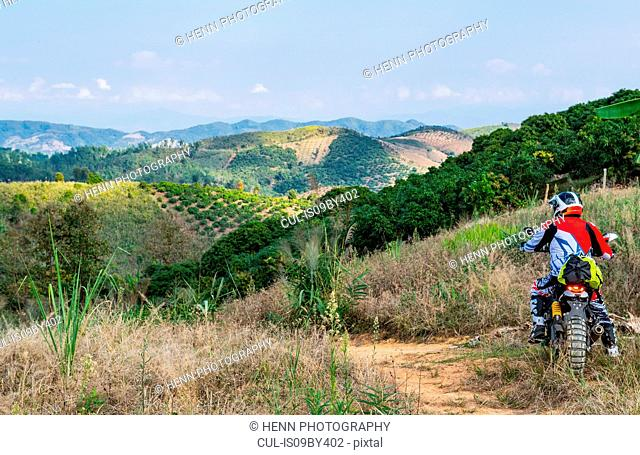 Biker riding scrambler on dirt track through Golden Triangle, Nan, Thailand