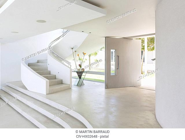 White foyer and spiral staircase in modern luxury home showcase interior