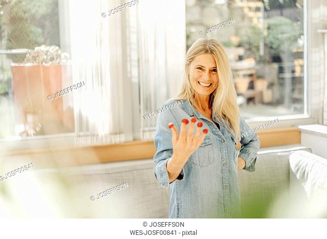 Portrait of happy woman with fruit on her fingertips