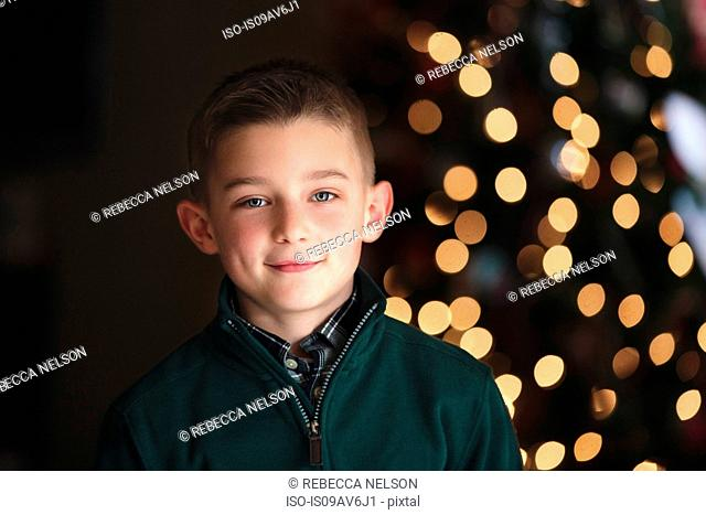 Portrait of boy in front of christmas tree looking at camera smiling