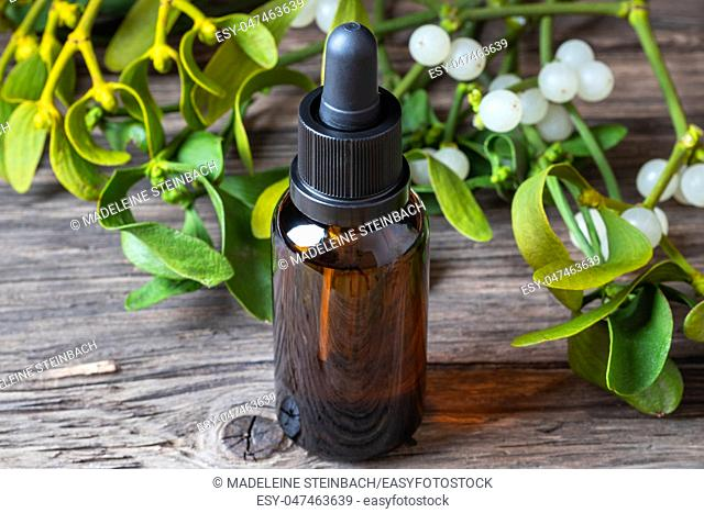 A bottle of herbal tincture with fresh mistletoe