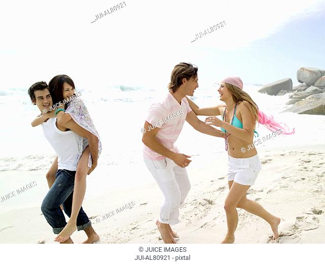 Two couples playing on beach