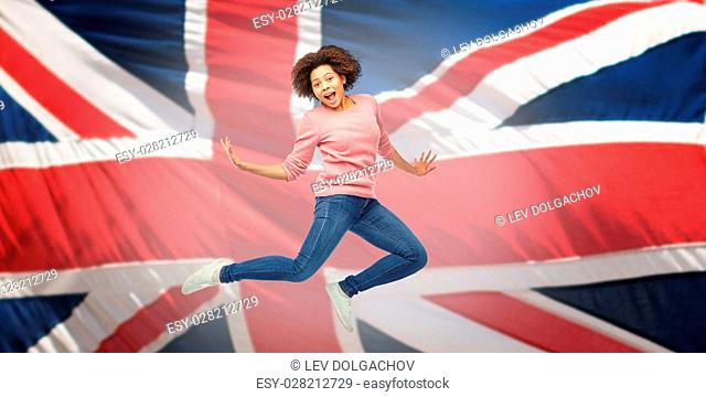 people, motion and action concept - happy african american young woman jumping over english flag background