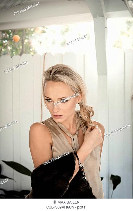 Glamorous and pensive mid adult woman carrying fur