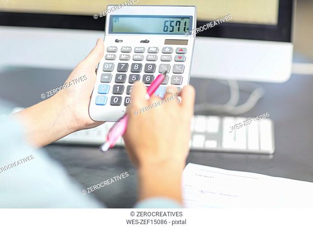 Woman at desk in office using calculator