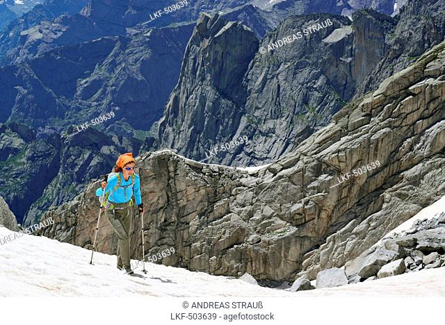 Woman ascending over snow, rocky mountains in background, Sentiero Roma, Bergell range, Lombardy, Italy