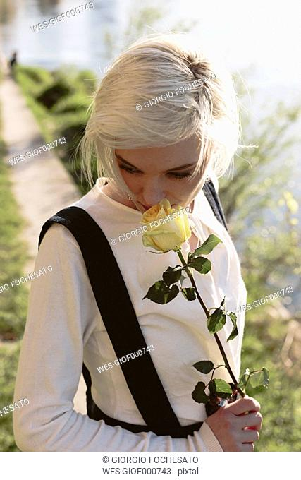 Blond woman smelling rose