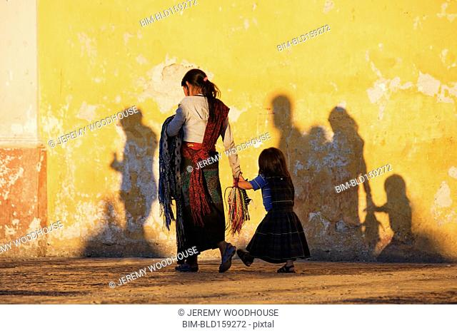 Mother and daughter walking near dilapidated wall