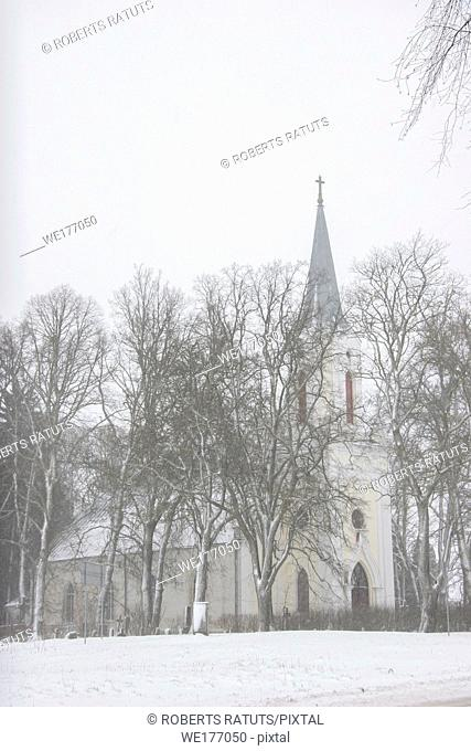 Church in snowfall. Winter in Barbele, Latvia. Church covered in snow. Winter landscape with snow covered church and trees. .