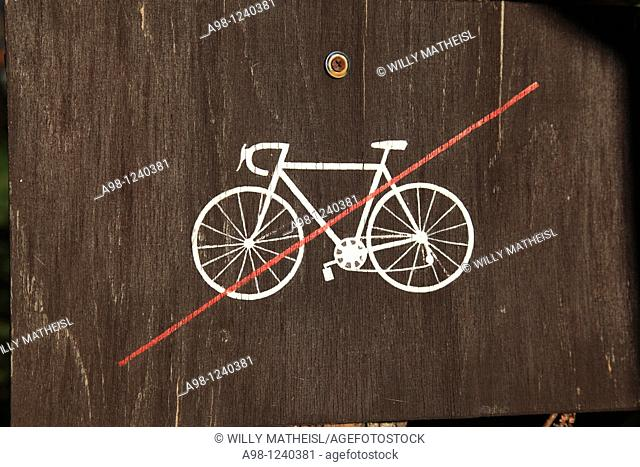 wooden man made sign showing 'bicycle prohibited', seen in the village Srni, Sumava, Bohemia, Czech Republic, Europe
