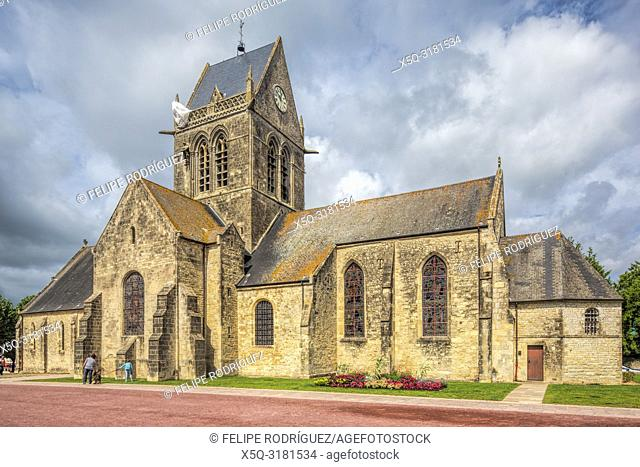 Church of Sainte-Mère-Église, Normandy, with the Parachute Memorial on the bell tower. The town played a significant part in the World War II Normandy landings...