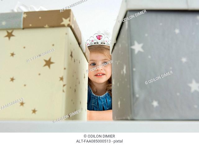 Girl with tiara in front of gift boxes