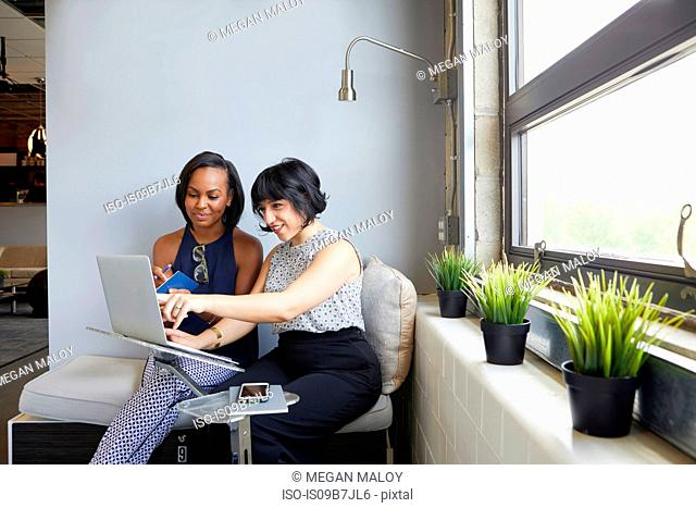 Two women sitting, working on laptop, on laptop stand