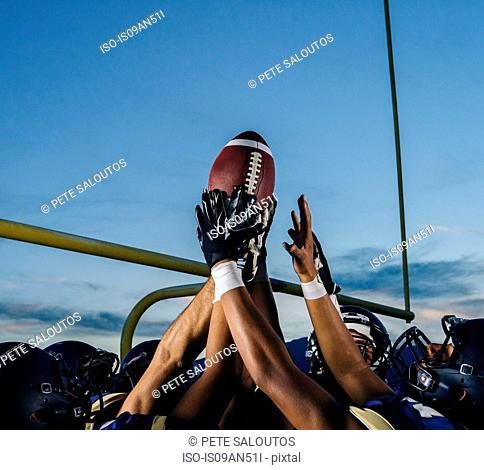 Victorious teenage and young male american football team holding up ball