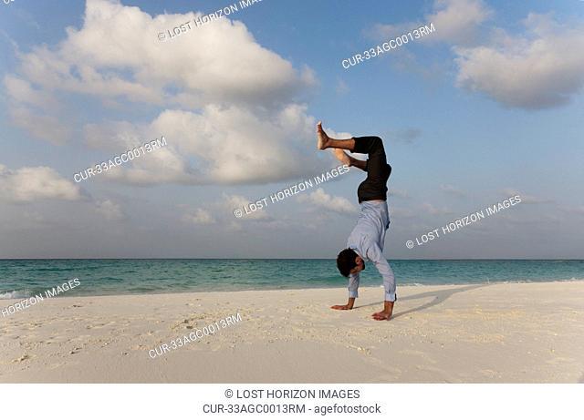 Businessman doing handstand on beach
