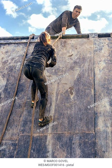 Participants in extreme obstacle race climbing wall