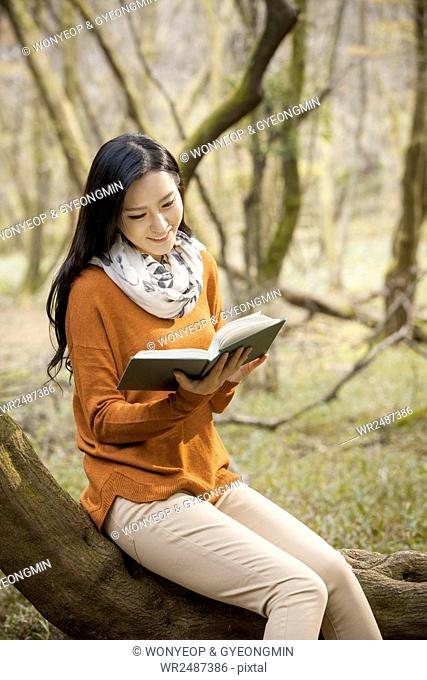 Young smiling woman sitting on a branch and reading a book in forest in fall