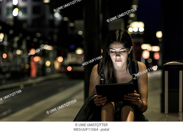 Portrait of young woman with headphones and tablet waiting at station by night