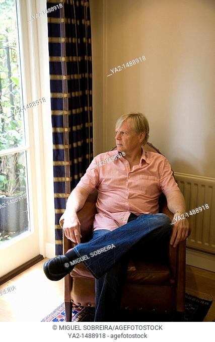 Mature man Looking out Window from Armchair