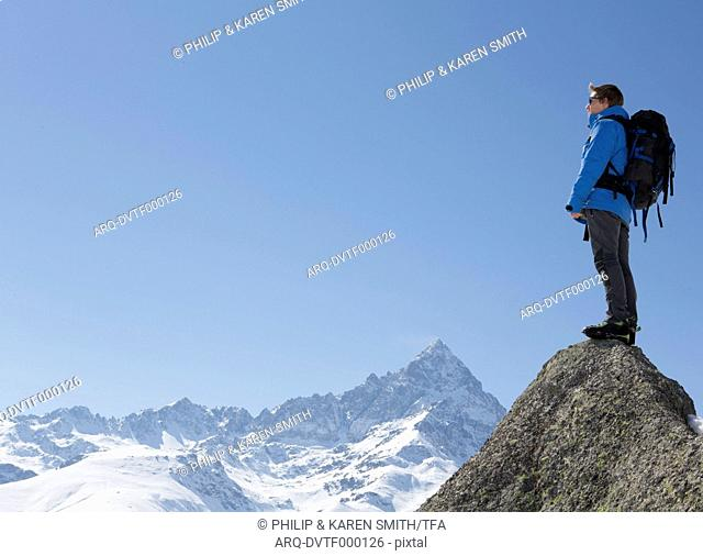 Portrait of mountaineer on summit\, above mtns