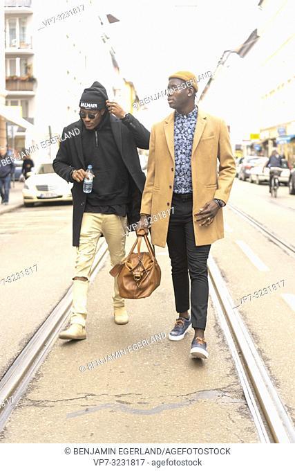 two stylish men walking on street in city, in Munich, Germany