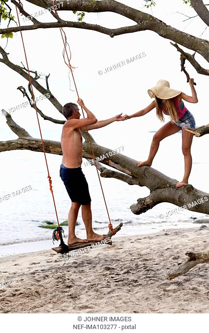 Father with teenage daughter playing on beach