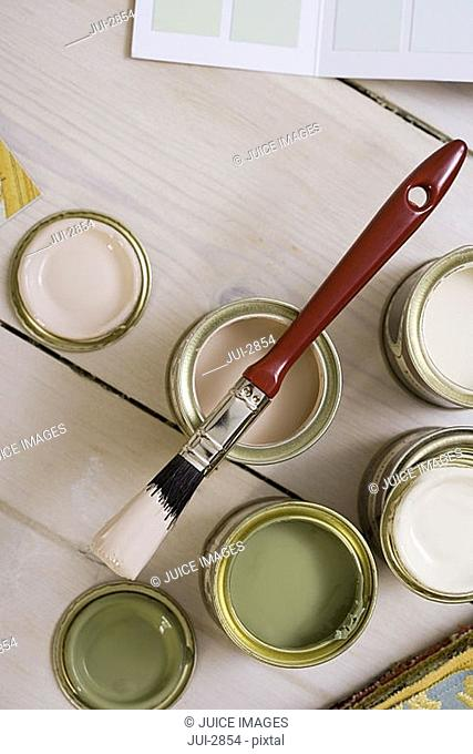 Small tins of paint and paintbrush on floor, close-up, overhead view still life