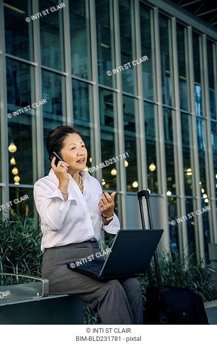 Businesswoman sitting on bench with suitcase talking on cell phone