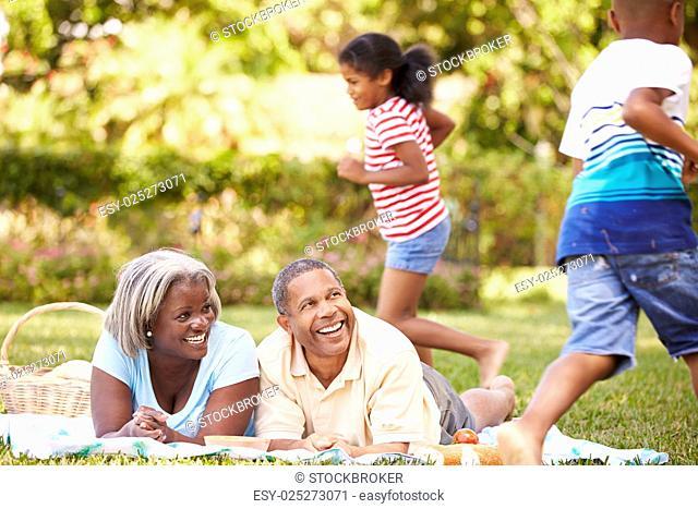 Grandparents And Grandchildren Having Picnic In Garden