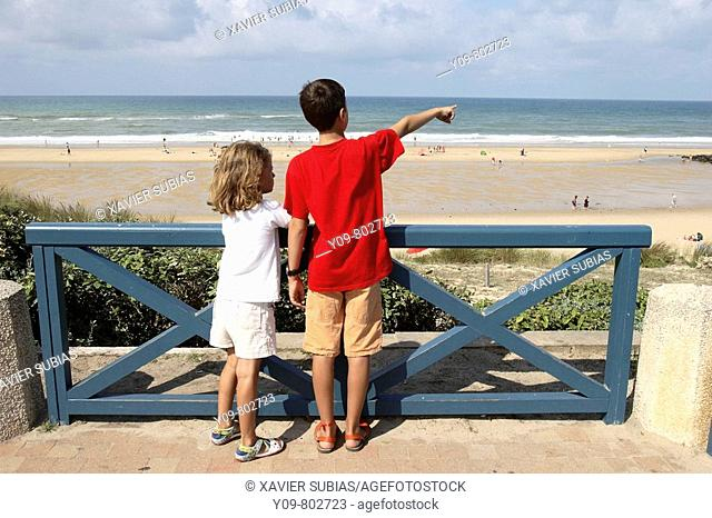 Boy and girl looking at the sea, Lacanau-Océan. Gironde, Aquitaine, France