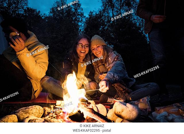 Group of friends sitting at a campfire, roasting marshmallows