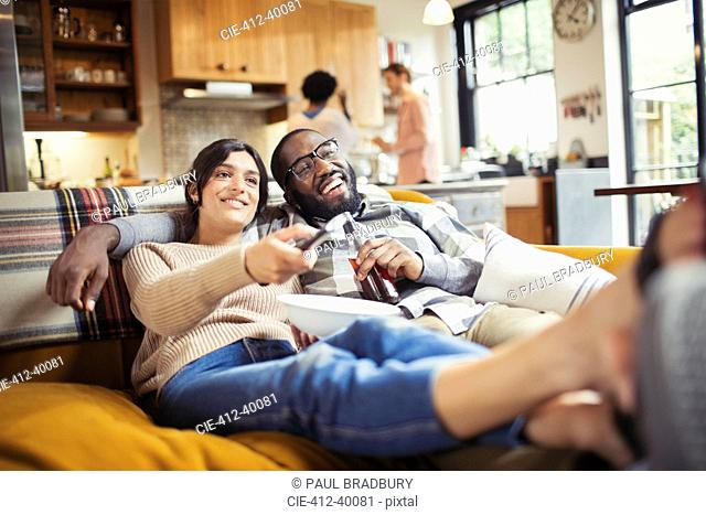 Smiling young couple watching TV, drinking beer and eating popcorn on living room sofa