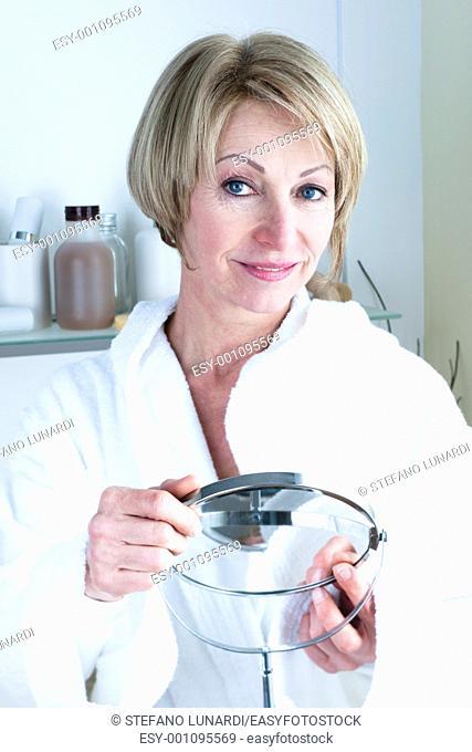 Beautiful mature woman holding mirror