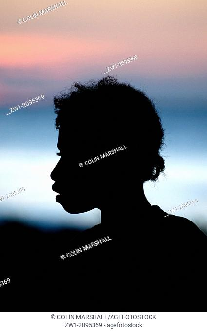 Silhouette of girl at sunset by sea at Warmandi in West Papua in Indonesia