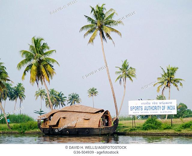 Traditional house boat contrasts with modern sign in Vembanad Lake near Alappuzha (Allepey). Kerala, India