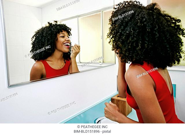 Mixed race woman applying makeup in mirror