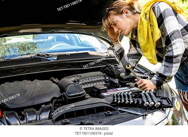 Frustrated woman repairing car