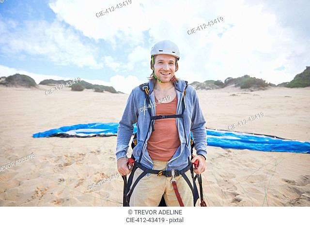 Portrait confident male paraglider on beach
