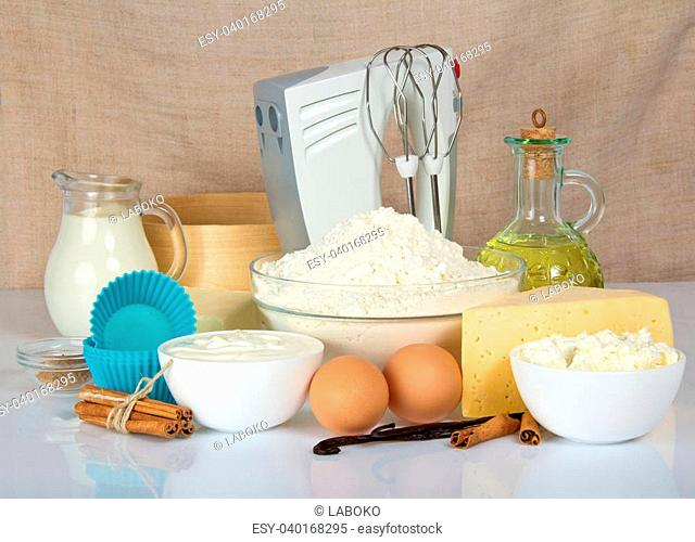 The cake pan, a mixer, a sieve and a products for dough, on a beige canvas