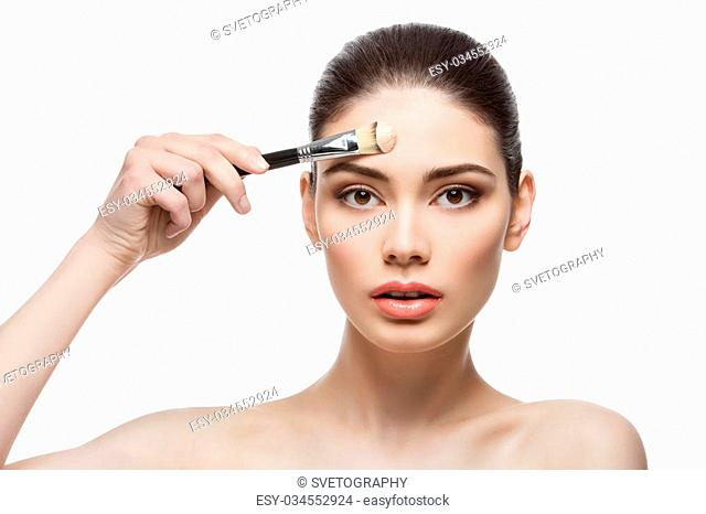 Beautiful young woman applying liquid foundation with brush. Isolated over white background. Copy space