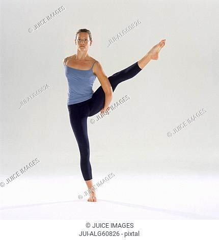 Woman balancing on one foot, with leg raised