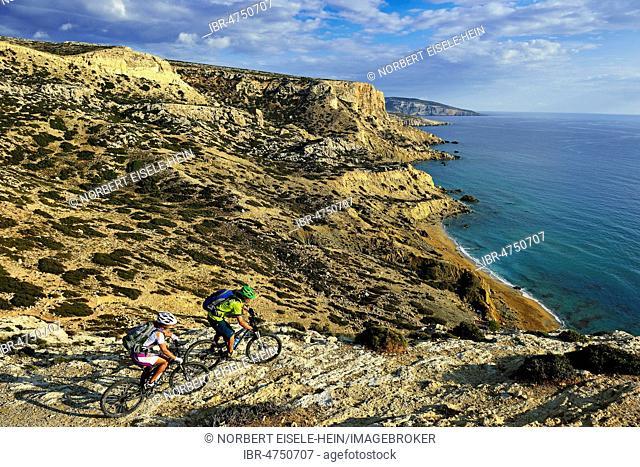 Two mountain bikers cycle along the rocky coast, Red Beach, Matala, Crete, Greece