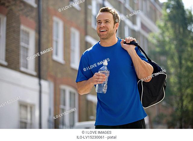 A young man walking down the street, carrying a sports bag and a bottle of water