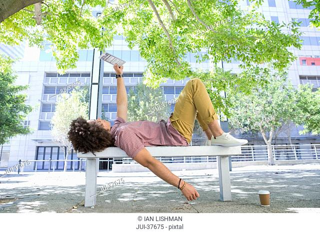 Young man laying on urban park bench and using digital tablet