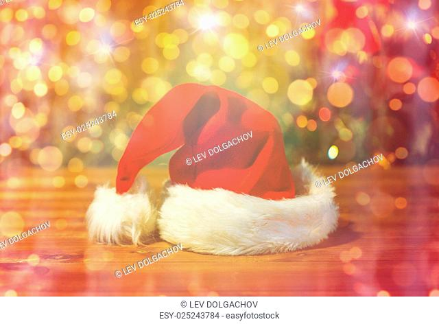 holidays, christmas, costume and tradition concept - close up of santa hat on wooden table over lights background