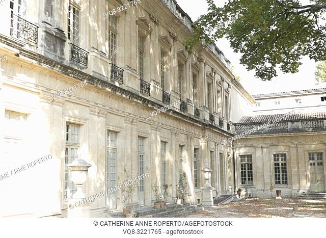 Gracious courtyard facacde of Musee Calvet, with repeating windows, pilasters, decorative carvings and elegant metal work balconies